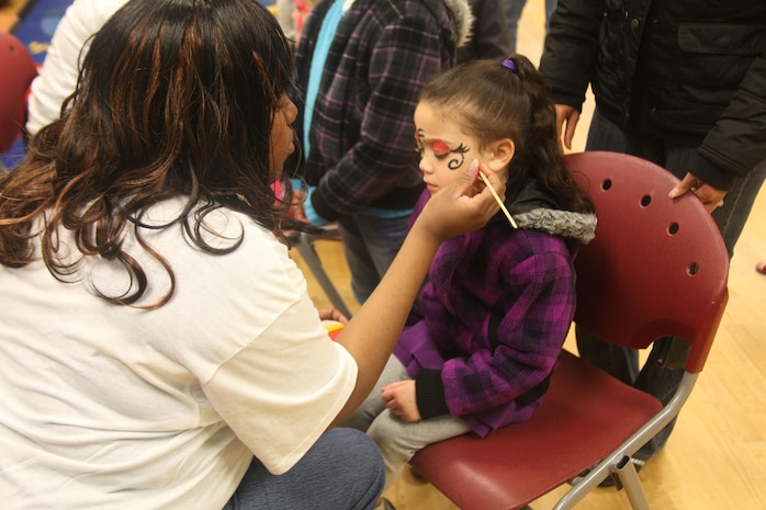 Sarah Harris, 4-years-old, gets her face painted by Tamika L. Curtis, th program assistant for the youth center, during the Eggstravaganza at the Laurel Bay Youth Center, March 23. Face painting was one of many activities offered during the celebration.