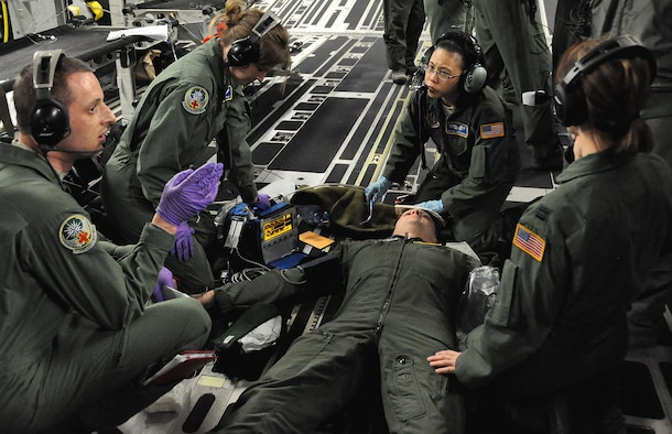 A team of Reservists from the 446th Aeromedical Evacuation Squadron treat Capt. Steven Smith, 446th AES flight nurse and training evaluator, during a C-17 training exercise April 7. Smith pretended to be a patient who fainted and vomited blood. This scenario was a test for a team of flight nurses and medical technicians. (U.S. Air Force Photo/Airman 1st Class Madelyn McCullough)