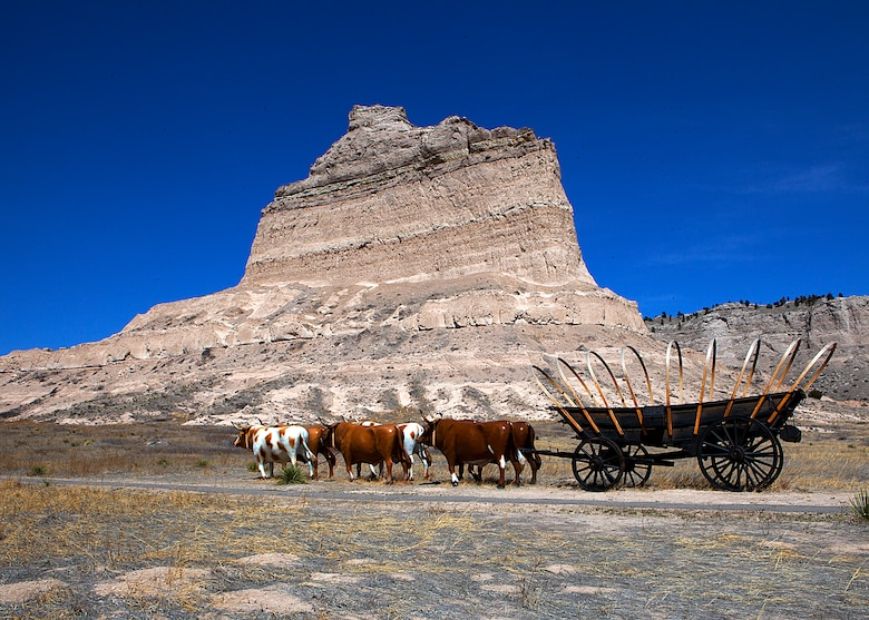 A static display of a horse drawn wagon is shown in front of Eagle Rock along the original Overland Trail at Scotts Bluff National Monument, Neb. (U.S. Air Force photo by Matt Bilden)