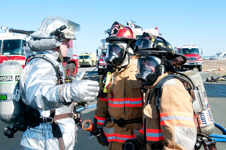 Tech. Sgt. Matt Drallette discusses fire tactics with members of the Sugar Grove Fire Department before their evolution on the simulated aircraft fire at the 167th Airlift Wing, April 6.  Members of the 167th Fire Department have to complete the burn trainer as part of an annual requirement.  Personnel from Sugar Grove FD were on base during the April unit training assembly to go over general tactics of aircraft firefighting. (U.S. Air Force photo by Tech. Sgt. Michael Dickson/Released)