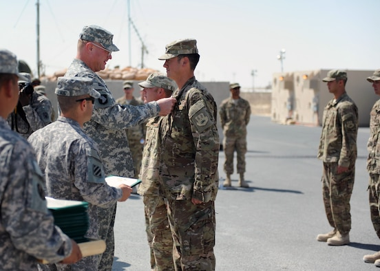SOUTHWEST ASIA -  Army Col. Randall McIntire, 69th Air Defense Artillery Brigade commander, awards Air Force Capt. Ben Thomas, 557th ERHS construction site officer in charge, with an Army Commendation Medal for his team's support of the 1-43 Air Defense Auxiliary Battalion, April 9. (U.S. Army photo/Capt. Steven Modugno)