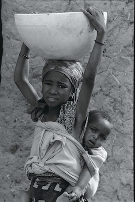 Throughout the region one sees young girls like this one carrying large containers of water on their heads as they carry a baby sister or brother on their back.  This girl is about nine years old.  She has never attended school.