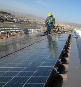 A contractor surveys his work atop a dining facility on Fort Bliss, Texas. Huntsville Center manages multiple types of projects on U.S. Army installations, like this facility-level solar project that was part of an Energy Savings Performance Contract.