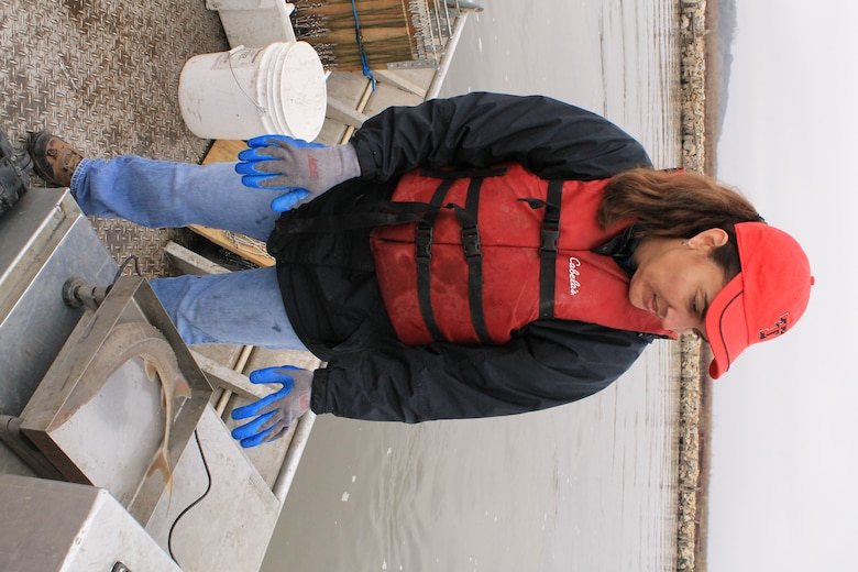 Omaha District Leadership Development Program participant and Public Affairs Specialist, Eileen Williamson weighs a shovelnose sturgeon during pallid sturgeon broodstock collection efforts with the Nebraska Game and Parks Commission on the Missouri River, April 8.