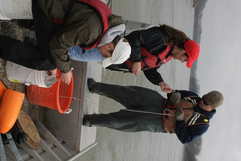 Omaha District Leadership Development Program participant and Engineer in the Hydrologic Engineering Branch, Josh Melliger hands LDP participant and Public Affairs Specialist, Eileen Williamson baited hooks to be clipped to trotlines as they are placed in the Missouri River during pallid sturgeon broodstock collection efforts with the Nebraska Game and Parks Commission, April 8.