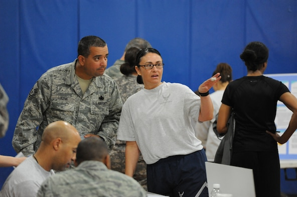 Capt. Tisha Cornett, 386th Expeditionary Medical Group, provides information to Master Sgt. Michael Lucena during the 386th Air Expeditionary Wing wellness fair Apr 13, 2013. Cornett organized the fair around Air Mobility Command's Comprehensive Airman Fitness model. (U.S. Air Force photo by Senior Master Sgt. George Thompson)