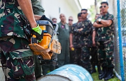 Philippine Air Force Technical Sgt. Arthuro Sumilhig prepares to cut through a barrel with the K-12 rescue saw April 8 during a rescue familiarization training at Clark Field, Philippines. The training was part of exercise Balikatan 2013, an annual bilateral training evolution aimed at ensuring interoperability of the Philippine and U.S. militaries during planning, contingency and humanitarian assistance operations.