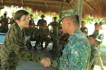 Chaplain of the U.S. Marine Corps, U.S. Navy Rear Adm. Margaret Grun Kibben, shakes hands with Philippine Marine Capt. Recto C. Pumares, Motor Transportation and Support Battalion, Combat Service Support Brigade, April 10 during a bilateral motor transportation, maintenance and welding expertise exchange as a part of the field training exercise of Balikatan 2013 at Camp O'Donnell, Philippines. BK13 is a bilateral joint exercise between AFP and U.S. forces designed to enhance interoperability, multinational cooperation and military-to-military relationships.