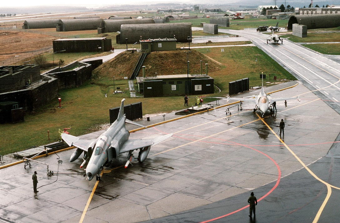 An F-4G Wild Weasel fighter (foreground) and an F-16 Fighting Falcon are serviced on the flight line prior to departing for Saudi Arabia during Operation Desert Shield. (U.S. Air Force photo/Tech. Sgt. Fernando Serna)