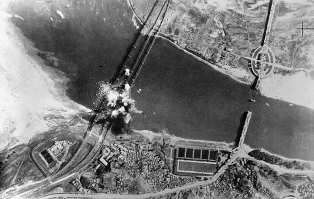 Air view of bombs dropped by U.S. Air Force, exploding on three parallel railroad bridges across Han River, southwest of Seoul, capital of the Republic of Korea. Bridges were bombed early in war to delay advance of invading North Korean troops. (DoD/National Air and Space Museum, #50-9025-306-PS)