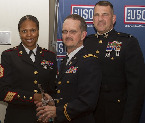 FORT BELVOIR, Va. – Gunnery Sgt. Tawanda Hanible, Diversity Operations Chief, Office of Diversity, Marine Corps Recruiting Command, receives the C. Haskell Small Award for volunteerism, during the USO of Metropolitan Washington Annual Celebration of Volunteers at the officer's club, here, Saturday. Presenting the award is Army Col. Charles Callahan, Commander, Fort Belvoir Community Hospital. Hanible, a Chicago native, is the founder and chief executive officer of Operation Heroes Connect, a non-profit organization that provides at risk youth with positive role models through volunteer service members and veterans. Also pictured is Col. Robert G. Golden III, chief of staff, MCRC.