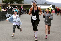 Amy Devine, center, and her daughters Holly, left, and Sydney, right, run to the finish line as a family during the Heartbreak Ridge Marathon here April 13. Holly, 6-years-old, Sydney, 9-years-old, and their mother, Devine, traveled from Riverside to compete in the annual race.