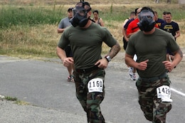 Sgt. Artur Shvartsberg, left, and Cpl. Stephen Johnson, right, run the trails of the Heartbreak Ridge Half Marathon, here, while wearing boots, utilities and gas masks April 13. Shvartsberg is a combat videographer with 1st Marine Division's Combat Camera here. Johnson is a radio operator with 9th Communication Battalion here.