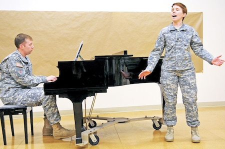 """Staff Sgt. Jennifer Champagne, accompanied by Spc. Wilson Flory, sings Regina Spektor's """"Lady"""" during a 1st Infantry Division Band recital March 28 at the band's headquarters at Fort Riley.  The performances featured ragtime, jazz and pop selections from a variety of musicians.  The band is set to host regular recitals at the end of every month.  For more information on the recitals, follow the 1st Inf. Div. Band on Facebook."""