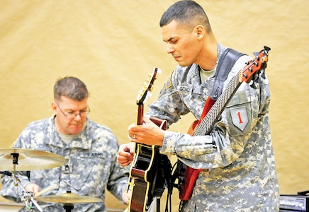 Staff Sgt. Andrew Goncalves goes back and forth between the bass and guitar during a 1st Infantry Division Band recital March 28 at the band's headquarters at Fort Riley, as Sgt. 1st Class Robert Davidson plays the drums.  The two were part of a trio that played a variety of jazz selections.  The band is set to host regular recitals at the end of every month.  For more information on the recitals, follow the 1st Inf. Div. Band on Facebook.