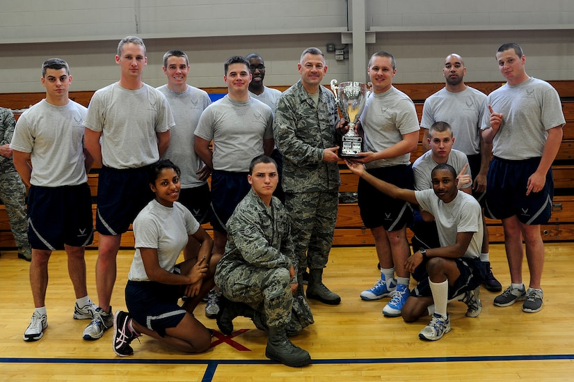 Col. Richard McComb, Joint Base Charleston commander, gathers with Airmen, from Dorm 473 and the Dorm Challenge trophy April 12, 2013, at the Fitness Center at Joint Base Charleston - Air Base, S.C. The quarterly Dorm Competition is a Wing initiative intended to encourage and incorporate all aspects of Comprehensive Airman Fitness, while encouraging resident interaction and camaraderie. The Dorm Challenge consisted of push-ups, sit-ups, cornhole and a game of dodgeball. (U.S. Air Force photo/Staff Sgt. Rasheen Douglas)