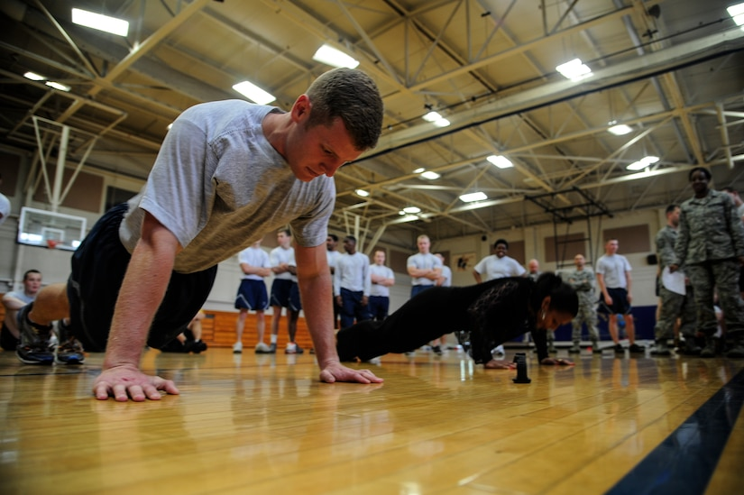 Senior Airman Matt Knopf, 628th Medical Group health services management technician, competes against Barbara Davis, 628th MDG budget analyst, to do as many push-ups as possible during the Dorm Challenge April 12, 2013, at the Fitness Center at Joint Base Charleston - Air Base, S.C. The quarterly dorm competition is a Wing initiative intended to encourage and incorporate all aspects of Comprehensive Airman Fitness, while encouraging resident interaction and camaraderie. The Dorm Challenge consisted of push-ups, sit-ups, cornhole and dodgeball. (U.S. Air Force photo/Staff Sgt. Rasheen Douglas)