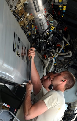 Airman 1st Class Adam Schaetzl (right) and Staff Sgt. Brody Bundy, 36th Expeditionary Aircraft Maintenance Squadron weapons load technicians, secure a training AGM-86C Conventional Air-Launched Cruise Missile inside the belly of a B-52 Stratofortress during a load demonstration at Andersen Air Force Base, Guam, April 16, 2013. All EAMUs deployed to Andersen have to pass a load inspection within 10 days of arrival as part of a U.S. Pacific Command requirement to ensure all tools and equipment are mission ready. Maintainers also obtain munitions-loading experience in both a training and tropical environment. (U.S. Air Force photo by Senior Airman Benjamin Wiseman/Released)