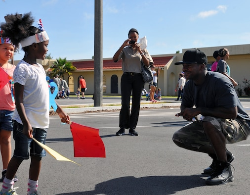 Tech. Sgt. Bryan Hawk, 36th Wing Legal Office civil law NCO in charge, smiles at his daughter during the Month of the Military Child parade at the child development center on Andersen Air Force Base, Guam, April 12, 2013. The Month of the Military Child was created by former Defense Secretary Caspar Weinberger to underscore the important role children play in the armed forces community. (U.S. Air Force photo by Airman 1st Class Adarius Petty/Released)
