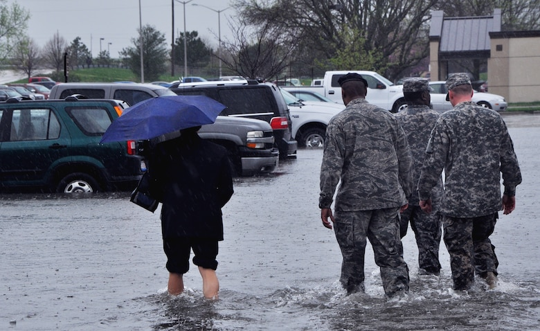 Servicemembers help a civilian to her car at Scott April 18, 2013 after rain dumped 5.2 inches on the base, causing floods and damage to vehicles and buildings. Throughout the day, servicemembers helped move cars from the flooded areas, while security forces members helped people exit the base and civil engineers assessed damage. (U.S. Air Force photo/Airman Megan Friedl)