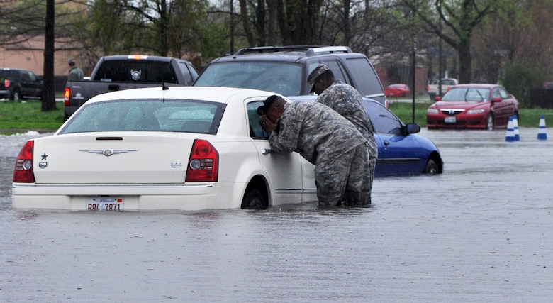 Servicemembers checked on vehicles at Scott AFB April 18, 2013 as 5.2 inches of rain fell in five hours. (U.S. Air Force photo/Airman Megan Friedl)