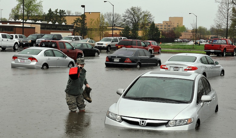Workers from Bldg. 1900 found their cars swamped in the parking lot after heavy downpours at Scott Air Force Base, Ill., April. 18, 2013.  In total, 5.2 inches of rain deluged the low-lying areas of the base, forcing several roads to close and early release of some workers. Several Soldiers helped coworkers move their cars from the flooded areas.  (U.S. Air Force photo/Airman 1st Class Jaeda Waffer)