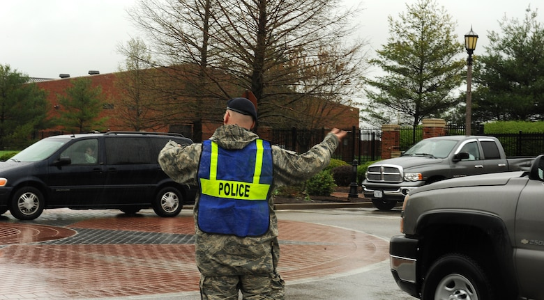 A 375th Security Forces Squadron patrolman directs traffic on Hangar Road after flooding closed several streets on Scott Air Force Base, Ill., April. 18, 2013. Severe weather dumped 5.2 inches of rain in five hours.  Base roads got congested when unit leaders granted early release of workers, due to deteriorating driving conditions. Roads were clear by 4 p.m. (U.S. Air Force photo/Airman 1st Class Jaeda Waffer)
