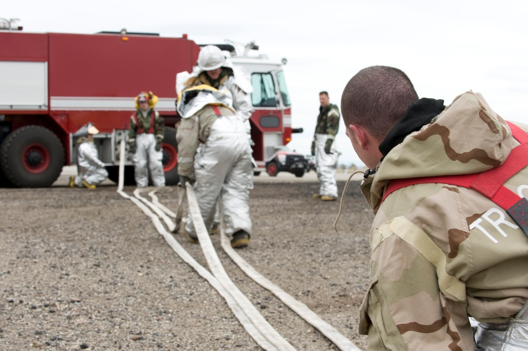 Firefighters put hoses away after a live-fire exercise at Mountain Home Air Force Base, Idaho, April 10, 2013. The firefighters worked together and demonstrated their mission-readiness. (U.S. Air Force Photo/Airman 1st Class Malissa Lott)