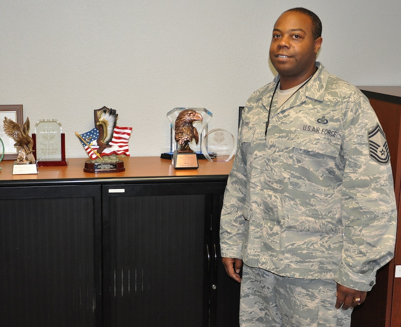 SMSgt Semaj McGhee stands in front of some of the awards presented to the Beale Command Post througout the years. Since 2010 this command post has won 17 individual and team awards and 4 MAJCOM level awards. (U.S. Air Force Photo/SrA Adam Hamar)
