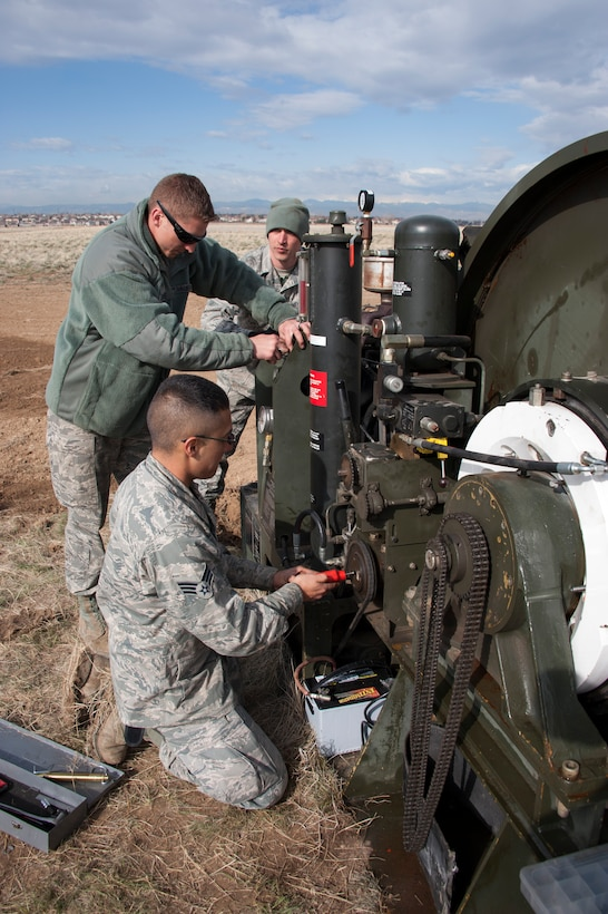 Civil Engineers and a Red Horse Unit are working together to install a BAK-12, Expeditionary Aircraft Arresting System on the main runway at Buckley Air Force Base.  The temporary system must be installed prior to any construction taking place on the runway and so the permanent arresting systems can be upgraded. Senior Airman Jesus Martinez (near) from the 460th Space Warning Squadron, Staff Sgt. Alex Atkins (center) from the 140th Wing and Staff Sgt. Issac Strickler from the 200th Red Horse unit adjust the braking system of the BAK-12 Aircraft Arresting system as part of the installation process.  (U.S. Air National Guard photo by Senior Master Sgt. John Rohrer)