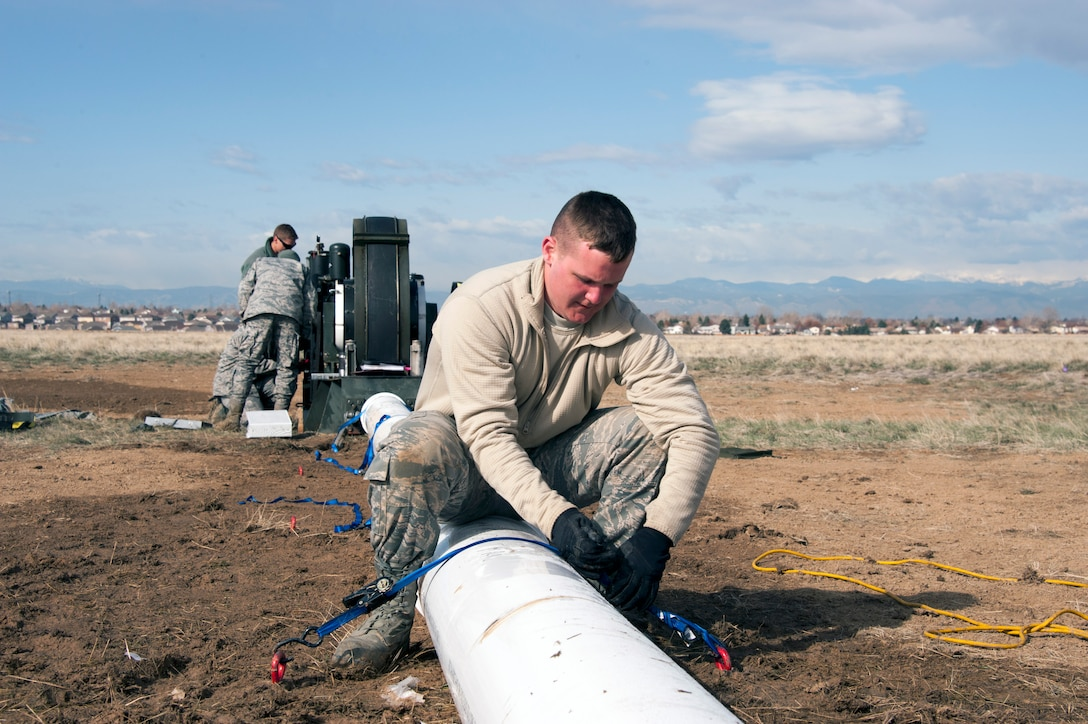 Civil Engineers and a Red Horse Unit are working together to install a BAK-12, Expeditionary Aircraft Arresting System on the main runway at Buckley Air Force Base.  The temporary system must be installed prior to any construction taking place on the runway and so the permanent arresting systems can be upgraded. Senior Airman Jordan Deady, from the 200th RED HORSE Unit, Detachment 1, out of Mansfield, Ohio, ties down the covering for the barrier tape on the arresting system as other civil engineer crewmen adjust the braking system behind him.  (U.S. Air National Guard photo by Senior Master Sgt. John Rohrer)