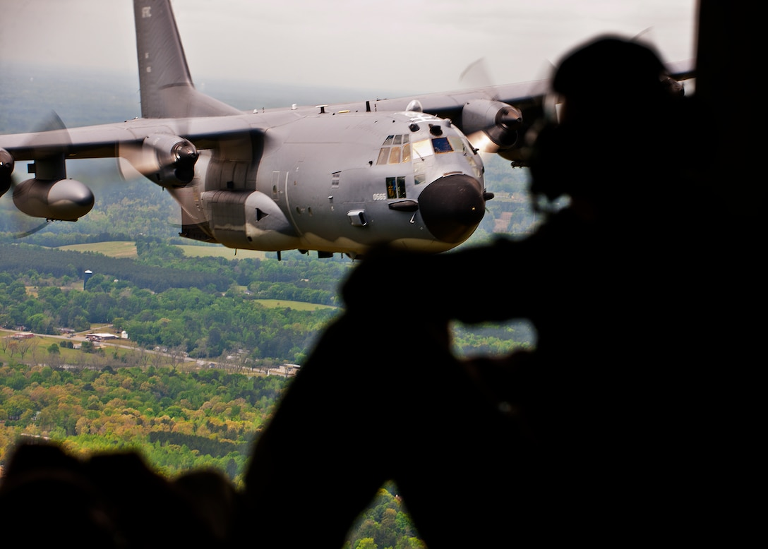 """A loadmaster with the 919th Special Operations Wing admires his aircraft, the MC-130E Combat Talon I, in flight one last time April 15 during its final flight before retirement.  The last five Talons in the Air Force belong to the 919th SOW and are scheduled to be retired at a ceremony April 25.  They will make one final flight to the """"boneyard"""" at Davis-Monthan Air Force Base, Ariz., by the end of the fiscal year.  (U.S. Air Force photo/Tech. Sgt. Samuel King Jr.)"""