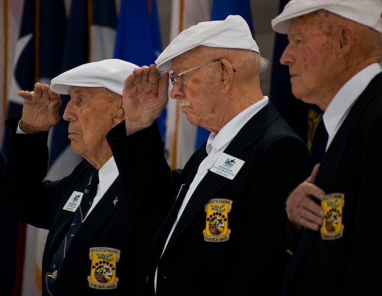 Doolittle Raiders, Col. Dick Cole, Lt. Col. Ed Saylor and Staff Sgt. David Thatcher, salute during the National Anthem at the 33rd Fighter Wing hangar dedication in honor of Saylor April 17 at Eglin Air Force Base, Fla.  After unveiling the plaque with his name on it, Saylor spoke about his experiences in the military and with the historic Raiders.  For the ceremony, an F-35A Lightning II and a Doolittle Raider B-25 were parked side by side in the hangar.  (U.S. Air Force photo/Samuel King Jr.)