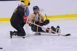 Mike McKenna (left), a project engineer with the U.S. Army Corps of Engineers, Fort Drum Field Office with one of the sled hockey team players.