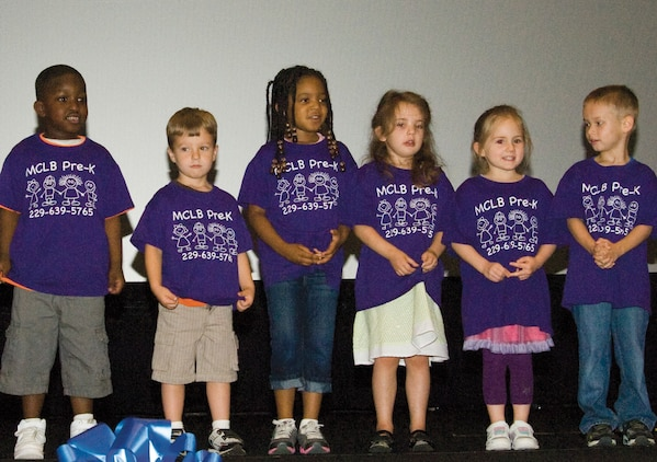 Children from the Child Development Center sing songs during the Child Abuse Awareness Month Proclamation ceremony held April 9 at the Base Theater, here.