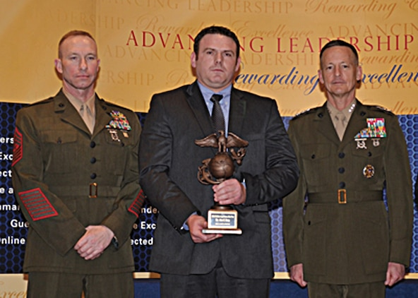 John Estep, center, logistics management specialist, Marine Corps Logistics Command, receives the Marine Corps' 2012 Civilian Logistician of the Year trophy during the Ground Logistics Excellence Awards Dinner held in Arlington, Va., March 14.