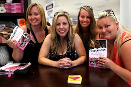 "Melissa Davis, left, Mollie Gross, center left, Abby Smith, center right, and Brianna Caskey, right, hold Gross' novel, ""Confessions of a Military Wife,"" during the Live, Laugh and Learn book signing event at the Pacific Views Marine Corps Exchange here April 19. Gross is a wife, author, comedienne and motivational speaker. The Live, Laugh and Learn tour features motivational presentations, book signing and author meet-and-greet events for military wives."