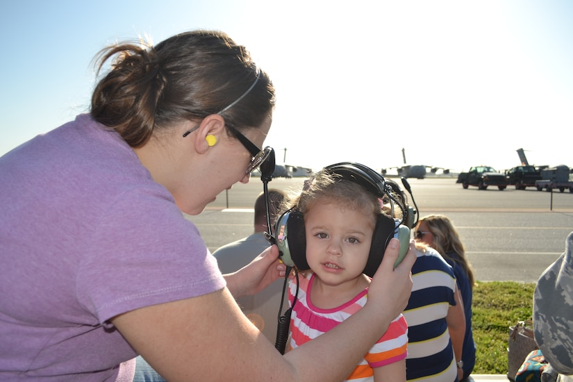 Doary, wife of Tech. Sgt. Marc Disbrow 437th Aircraft Maintenance Squadron Communication and Navigation Systems craftsman, places protective gear on her daughter Izzy during the 437th Aircraft Maintenance Squadron Spouses Tour, April 10, 2013 at Joint Base Charleston – Air Base, S.C.  The tour included informative briefings on AMXS, JB Charleston, C-17 Globemaster III capabilities and also consisted of various maintenance equipment set-up to include an aircraft tow vehicle, a bread truck (vehicle used to shuttle personnel around the flightline), and a tire chariot. (U.S. Air Force photo/ Tech. Sgt. Marc Disbrow)