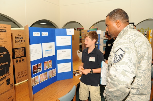 Master Sgt. Malik Franklin, 36th Munitions Squadron flight chief,  listens to a seventh grader explain his science fair project at Andersen Middle School on Andersen Air Force Base, Guam, April 4, 2013. The science fair showcased the students' creativity and scientific knowledge. (U.S. Air Force photo by Airman 1st Class Adarius Petty/Released)