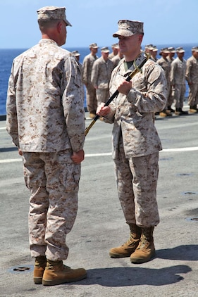 USS RUSHMORE (April 13, 2013) First Sgt. Bradley Simmons, sergeant major, Combat Logistics Battalion 15, 15th Marine Expeditionary Unit, passes a non-commissioned officer's sword to Lt. Col. John Wiener, commanding officer, CLB-15, 15th MEU, during the relief and appointment ceremony on the flight deck of USS Rushmore, April 13. The ceremony welcomed Sgt. Maj. JohnPaul Doring and bid farewell to Simmons. The 15th MEU is comprised of approximately 2,400 Marines and sailors and is deployed as part of the Peleliu Amphibious Ready Group. Together, they provide a forward-deployed, flexible sea-based Marine Air Ground Task Force capable of conducting a wide variety of operations ranging from humanitarian aid to combat. (U.S. Marine Corps photo by Cpl. Timothy Childers/Released)