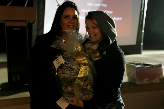 Kristine Schellhaas, left, presents Emily Sollars, right, with a gift basket from the raffle during the Live, Laugh and Learn event at the Del Mar Beach Resort here April 19. The tour features motivational presentations, book signing and author meet-and-greet events for military wives. Schellhaas is the 2013 Camp Pendleton Military Spouse of the Year, founder of USMC Life and co-host of Semper Feisty Radio.