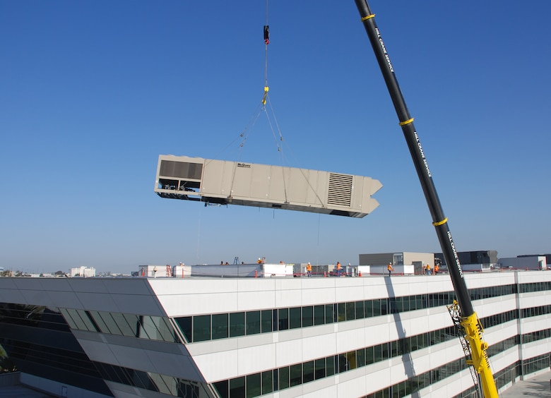 A heating and heating and air conditioning unit is removed from at top a building on Los Angeles AFB, April 20.  (Courtesy photo)