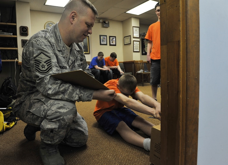 Master Sgt. William Sander, 509th Comptroller Squadron financial services superintendent, measures Camren's, 15, a Civil Air Patrol cadet, sit-and-reach physical assessment, March 28, 2013, in Sedalia, Mo. The cadet physical fitness training is aligned with the President's Challenge, a fitness program sponsored by the President's Council on Physical Fitness and Sports. (U.S. Air Force photo by Heidi Hunt/Released)