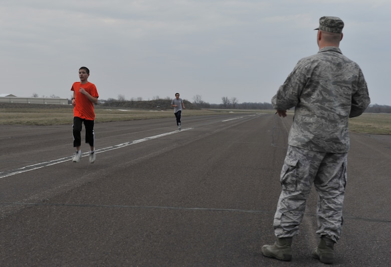 Master Sgt. William Sander, 509th Comptroller Squadron financial services superintendent, records run times for  Alex, 14, and Breandan, 13, Civil Air Patrol cadets during their physical fitness assessment, March 28, 2013, in Sedalia, Mo.. Sander also monitors for safety during all cadet activities. (U.S. Air Force photo by Heidi Hunt/Released)