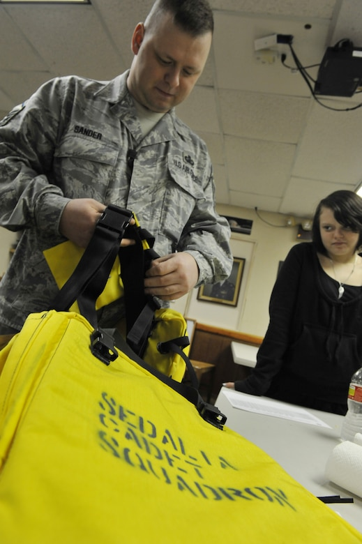 Master Sgt. William Sander, 509th Comptroller Squadron financial services superintendent, shows Cynthia, 14, how to properly prepare search and rescue equipment during a Civil Air Patrol meeting, March 28, 2013, in Sedalia, Mo. Students learn different skills to help them prepare for emergency communications and disaster relief. (U.S. Air Force photo by Heidi Hunt/Released)