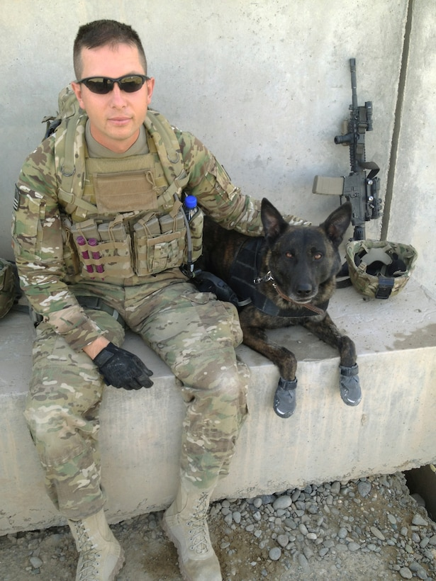 U.S. Air Force Staff Sgt. Robert Wilson, 366th SFS military working dog handler, and his dog Troll pause for a photo before heading out on a mission in the Kandahar Province during June 2012. The team led the Joint Task Force and Afghan National Army Soldiers through more than two miles of improvised explosive device infested poppy fields and extremely rough terrain in order to safely reach their final objective. (Courtesy photo)