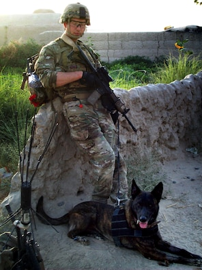 U.S. Air Force Staff Sgt. Robert Wilson, 366th SFS military working dog handler, and his dog Troll take a break after a village clearing operation in June 2012. Wilson and Troll primarily worked throughout the Kandahar province of Afghanistan assisting coalition forces with explosives detection assistance. (Courtesy photo)