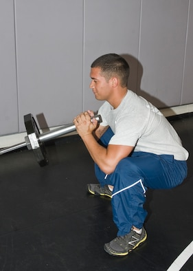 Airman 1st Class Joseph Kay, 7th Force Support Squadron, performs the second step in the barbell jammer exercise, April 17, 2013, at Dyess Air Force Base, Texas. (U.S. Air Force photo by Airman 1st Class Peter Thompson/Released)