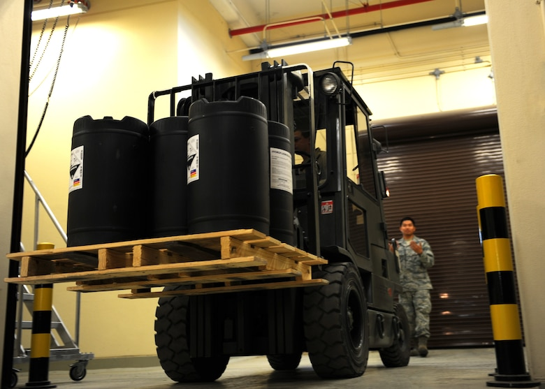 Airman 1st Class Michael Brown, 39th Logistics Readiness Squadron hazardous materials pharmacy technician, moves a pallet of hydrofluoric acid with a forklift as Senior Airman Marques Barcelona, 39th LGRS HAZMART pharmacy technician spots the movement at Incirlik Air Base, Turkey April 18, 2013. HAZMART pharmacy technicians operate a specially designed and equipped warehouse to maintain the base's hazardous material supplies. (U.S. Air Force photo by Senior Airman Chase Hedrick/Released)