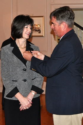 Tim Atkinson, husband of Michelle Cresswell-Atkinson, attaches the Senior Executive Service pin to her lapel during her SES induction ceremony April 18 in Harry Lee Hall at Marine Corps Base Quantico, Va. Cresswell-Atkinson serves as deputy commander for Resource Management and is the newest SES member at MCSC.